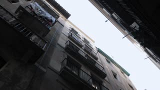 Steadicam shot: house with balconies in Barcelona's Gothic Quarter. Facades of old houses in the narrow streets of Barcelona. Traveling concept. Slow motion
