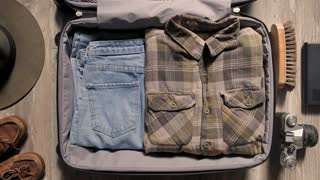 Stopmotion top view video of a young hipster adventurer preparing his suitcase for a trip around the globe, casually throws things in the bag, full of masculine accessories