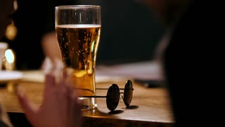 Story in bar - woman drink beer and talking with friend, black glasses on bar counter