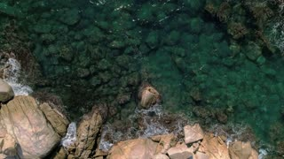 Straight down aerial drone shot from bird's view eye on beautiful and epic crystal clear waters of ocean or sea, waves hit rocks of mediterranean, amazing travel destination scenery