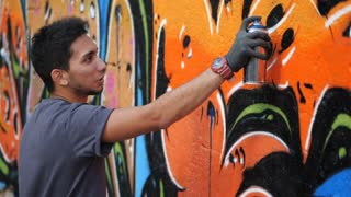 Street artist painting colorful graffiti on generic wall - Modern art concept with urban guy performing and preparing live murales with aerosol color spray - Sunny afternoon. Slow motion. Side view