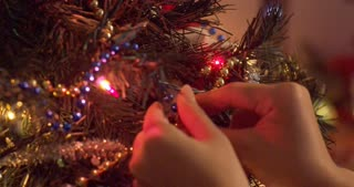 Stringing blue beads along other decorations on a glowing Christmas tree - slow motion