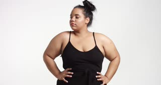 Strong confident beautiful plus size African American model in black one piece suit on white background