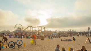 Stunning motion time lapse or hyper lapse at the Santa Monica pier with the sun setting, shot from the beach.