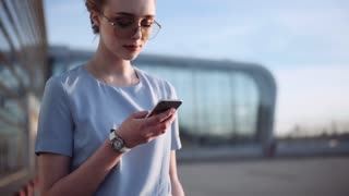 Stunning young business woman in a trendy look and sunglasses stands by the business center, waiting for someone, and uses her smartphone. Successful lifestyle, business woman, dealing contracts