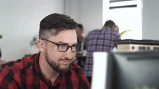 Stylish young architect sitting at desktop brainstorming ideas of new design