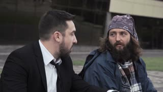 Successful rich young man eating on the sidewalk next to a bearded homeless beggar while waiting and looking up together