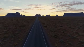Sunrise drone flight over a road towards Monument Valley
