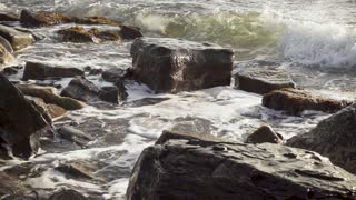 Super slow motion large stones, boulders smash a beautiful wave with foam and spray