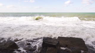 Super Slow Motion wave beautifully splits about boulders with foam