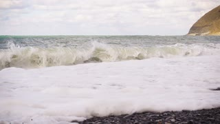Super slow motion wave beautifully with foam falls to the shore. Cliff in the frame