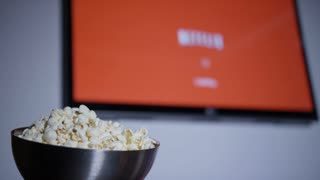 Taking popcorn out of the bowl while watching streaming movies