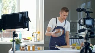 Talking professional chef in apron standing at kitchen table and cracking eggs into clear bowl, then adding milk and explaining recipe while recording cooking vlog on digital camera