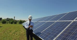 Technical expert in solar photovoltaic panels, with a tablet, remote control performs routine actions to monitor the system using clean, renewable energy. The concept of remote support technology.