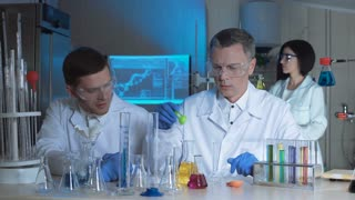 Technologists or scientist working in a chemical laboratory doing experiments with colorful solutions in beakers with two men working as a team in the foreground