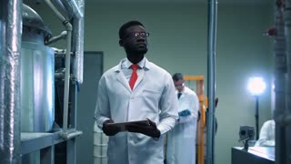 The African scientist standing on a factory and using the tablet. Horizontal indoors shot