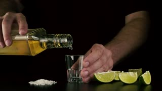 The barman's hand holds a shot on the table and pours the chilled tequila from the bottle. Slow mo