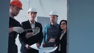 The builder measuring the doorway while talking to the managers and supervisor about the blueprint. Group of quality control weared hard hat and suit checks the sizes and quality of the performed