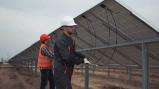 The builders connecting the solar energy panels with the wires