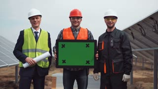 The builders standing near the solar panels and holding a frame for copy space