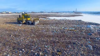 The bulldozer working at the city landfill. Drone. 4K.