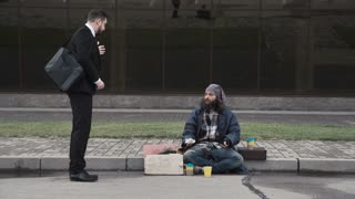 The businessman banishes the bearded homeless man and throws back his cup with money