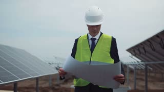 The businessman or architect wearing the helmet and looking into the plan on solar panels construction site. Then he looking to the camera and smile