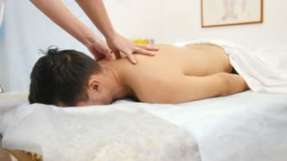 The doctor does massage back and shoulders the man at physiotherapy