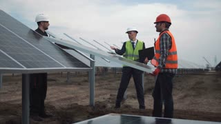 The engineer controls installation process of solar batteries, two employees in a uniform and in hardhat