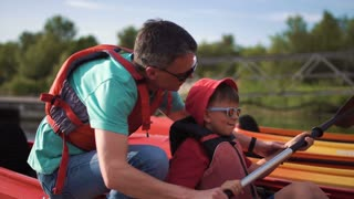 The father teaches the son on pier how to use an oar in a kayak
