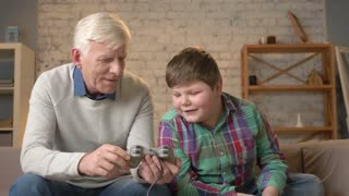 The grandson teaches grandfather to play the console game. An elderly man is learning how to play a fighting video game. Home comfort, family idyll, cosiness concept, difference of generations 60 fps