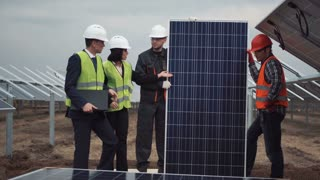The group of people standing and holding a solar energy panel while looking at camera between row of panels on solar farm. Main engineer explain how to setup panels using laptop