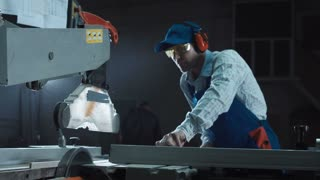 The joiner in uniform and protective equipment saws the pieces of a wooden plate on a sawing machine. Close movement stabilized shot