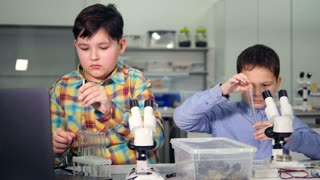 The mutual work of young scientists boys in the laboratory. Close-up. 4K.