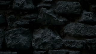The old brick wall background. Ancient building in gothic quarter of Barcelona. Slow motion. the camera moves from right to left