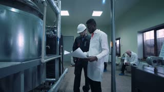 The scientist and an engineer walking in a factory with the blueprint. Horizontal indoors shot