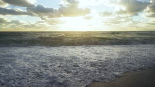 The sun and the sun's rays on the cloudy sky illuminate the stormy ocean and the shore slow motion
