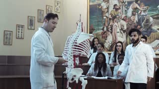 The tutor explaining the anatomy on a dummy to mixed ethnic group of students
