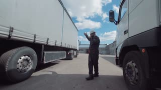 The warehouse worker showing to the driver where to park the truck