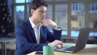 thoughtful guy reading documents on screen laptop. Caucasian professional businessman use computer in office or at home