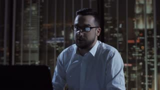 Thoughtful man in glasses sitting at laptop and working late in office making videocall