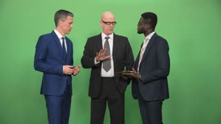 Three mixed ethnic males businessman in suits standing in circle and having discussion on green background