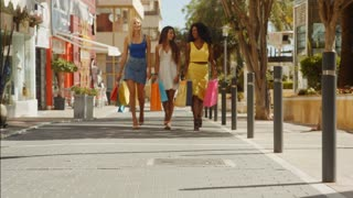 Three women walking towards camera with shopping bags in town
