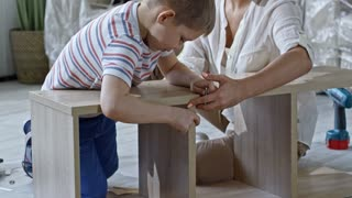 Tilt up of little boy driving screws into wooden shelf while young beautiful mother helping and smiling