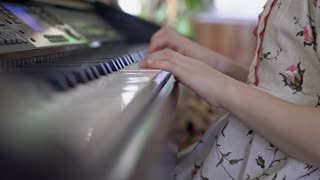 Tilt up of little girl with concentration on face playing melody on piano