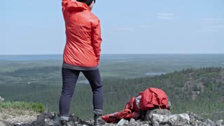 Tilt up rear view of woman tourist standing on mountain top, waving and holding smoke grenade burning with red