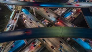 Time lapse aerial view of busy highway, freeway, motorway, urban city transportation junction, heavy traffic jam congestion, rush hour, cars passing with multiple lanes of traffic.