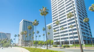 Time lapse in motion (hyper lapse) on a sunny blue sky day with high rise office buildings in Fashion Island shopping district located in Newport Beach, California with palm trees and cars in the foreground.