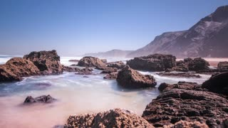 Time lapse of beautiful tide ocean on rocky shore. Foam sea waves splashing on rock cliff. Tide sea blue water on rocky shore. Water rocks. Rocks in water. Sea breeze above waves splash