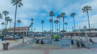 Time-lapse or hyperlapse at Newport Pier entrance in Newport Beach, California with clouds racing overhead and palm trees, tourists and cars in the background.